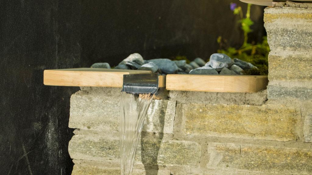 Wasserfall aus Edelstahl läuft durch Holzabdeckung
